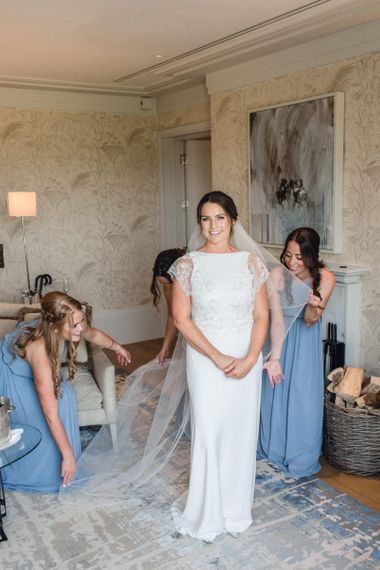 Bride Getting Ready in Charlie Brear Torum Wedding Dress with Bridesmaids in Blue Dresses