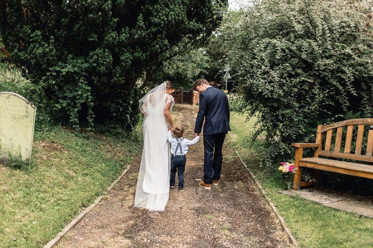 Bride  in Charlie Brear Torum Wedding Dress, Groom and Little Boy Holding Hands