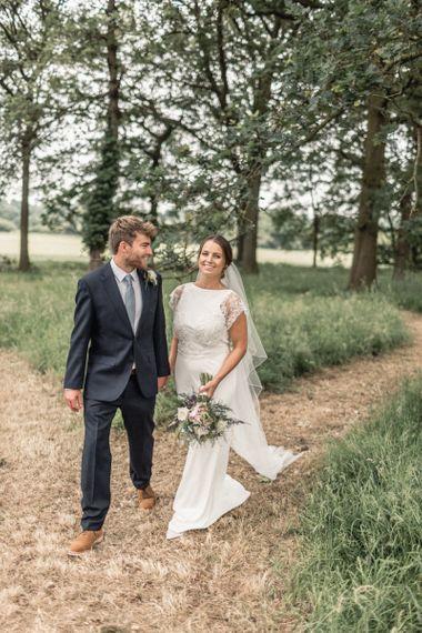 Bride  in Charlie Brear Torum Wedding Dress and Groom in Navy Suit