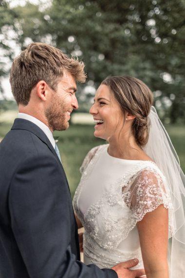 Laughing Bride  in Charlie Brear Torum Wedding Dress and Groom in Navy Suit