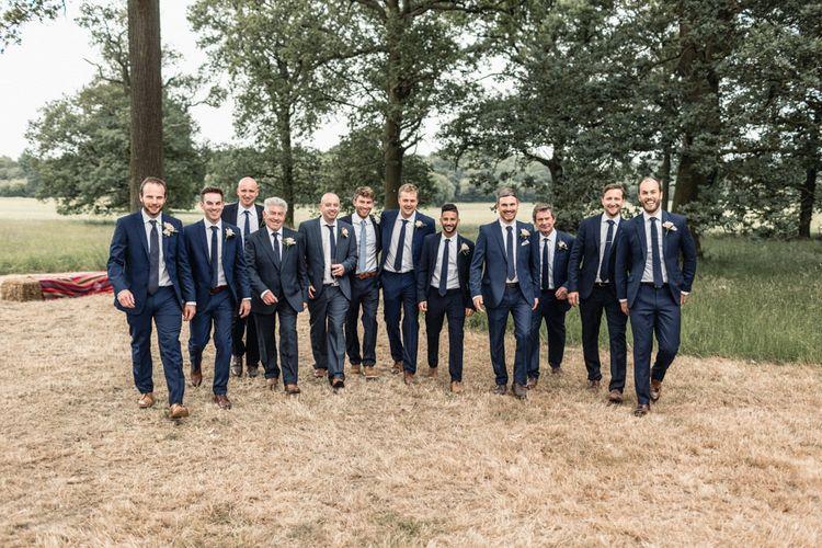 Groomsmen in Navy Blue Suits Walking Through the Fields