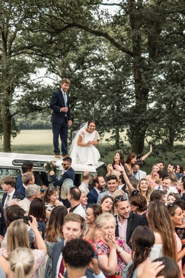 Bride in Charlie Brear Torum Wedding Dress  and Groom in Navy Suit Standing on Top of a Range Rover with Wedding Guests Surrounded
