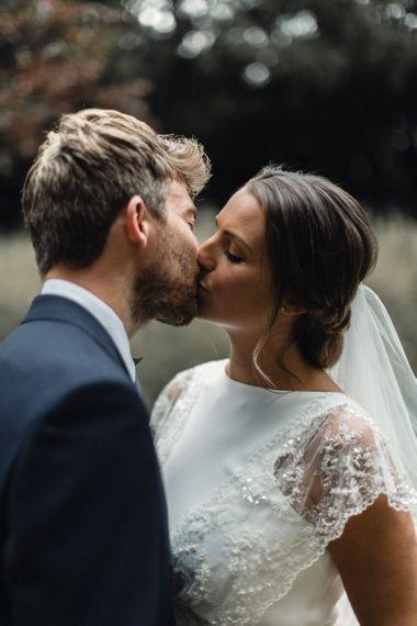 Bride in Charlie Brear Torum Wedding Dress Kissing Her Groom in Navy Suit
