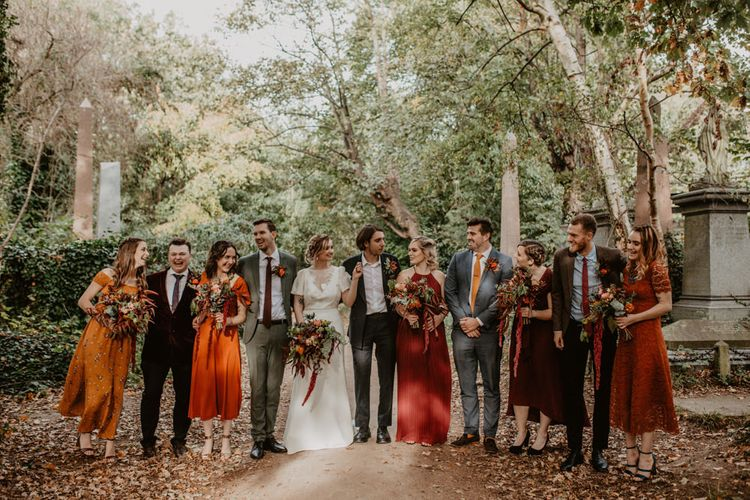 Wedding Party Portrait in the Cemetery with Autumn Leaves on the Floor