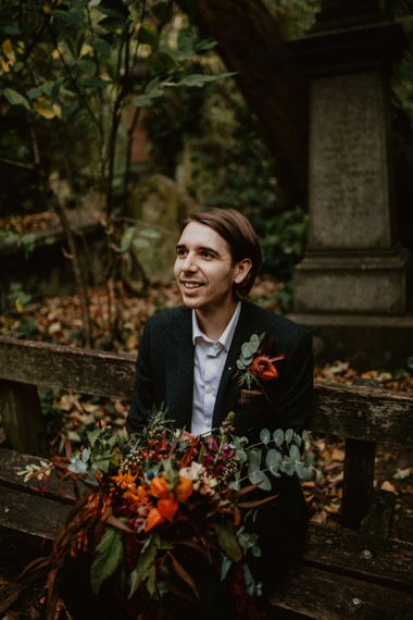 Groom in Black Suit Holding the Brides Oversized Wedding Bouquet