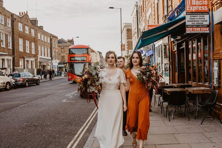 Bride and Bridesmaid Walking down the Urban Streets