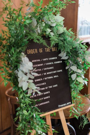 Pin Board Order of the Day Sign | Foliage Drapery | Neon Sign and Marine Green Rewritten Bridesmaids Dresses with Lace Cape Grace Loves Lace Gown | Alain Mbouche Photography