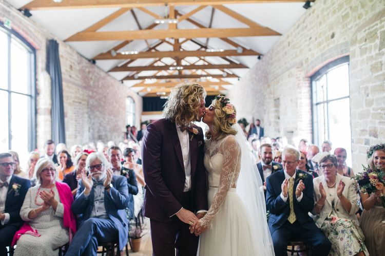 Wedding Ceremony with Bride in Separates and Flower Crown and Groom in Burgundy Suit Kissing