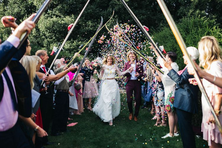 Confetti Moment with Bride in Separates and Flower Crown and Groom in Burgundy Suit Walking Under a Skies Tunnel