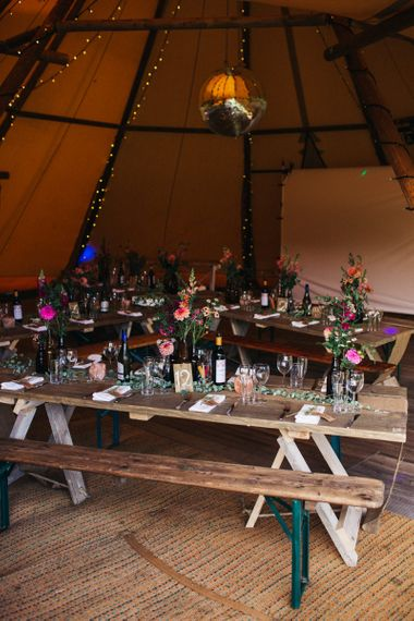 Wooden Tables with Bottles Filled with Colourful Flower Stems