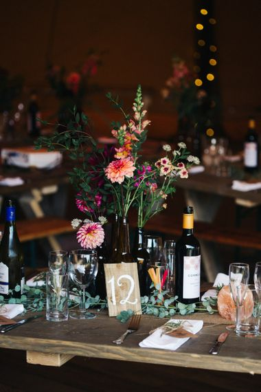 Table Centrepiece with Bottles Full of Colourful Flower Stems