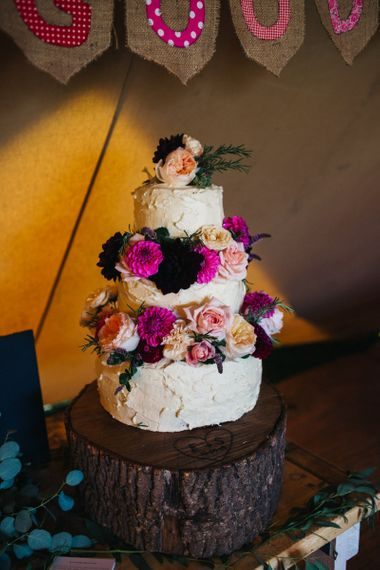 Buttercream Wedding Cake with Colourful Flowers Decor on a Tree Slice Cake Stand