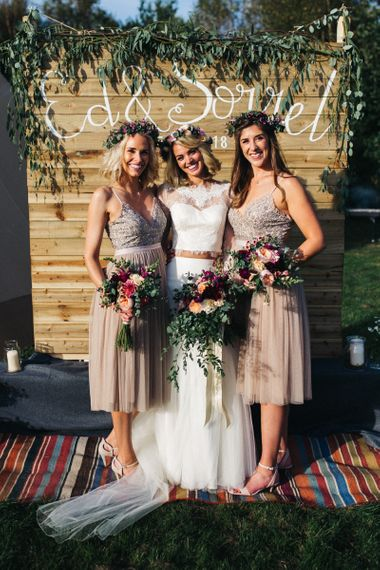 Bridesmaids in Needle & Thread Dresses with Bride in Separates Standing in Front of a Wooden Backdrop