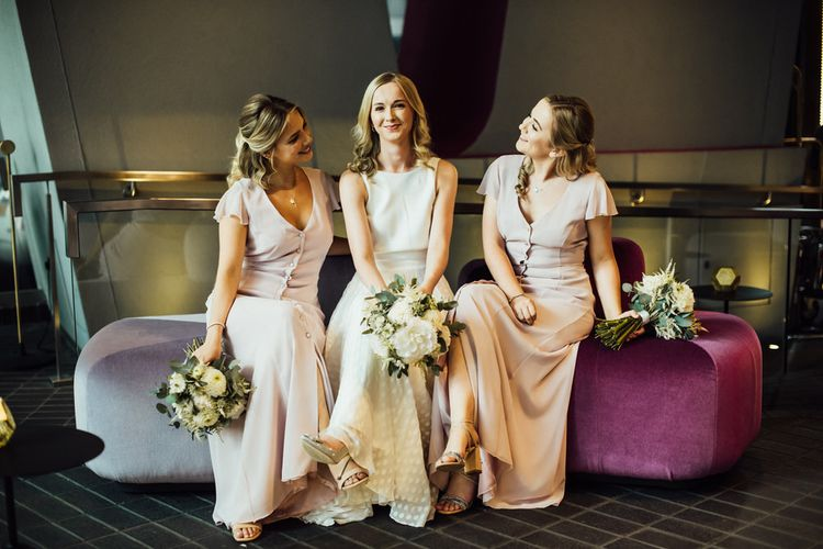Bride in Manolo Blahnik Wedding Shoes and Bridesmaids in Nude Dresses with White Dahlia and Peony Wedding Flowers
