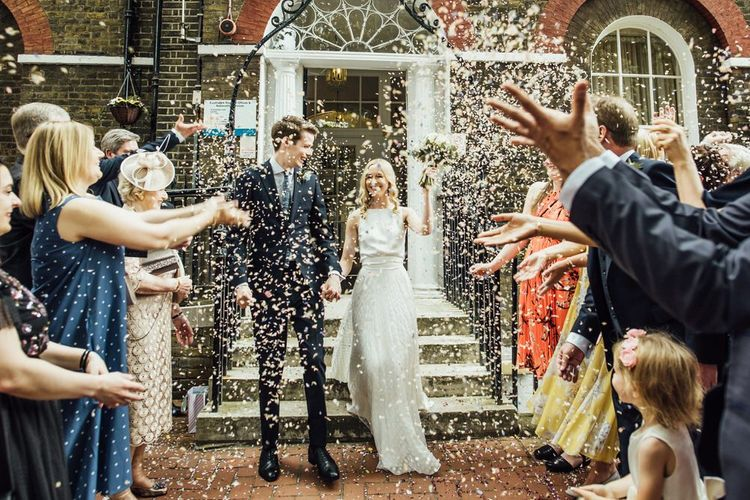 Confetti Shot at Summer City Wedding Ceremony with Satin Wedding Dress Removable Polkadot Overskirt and Manolo Blahnik Wedding Shoes