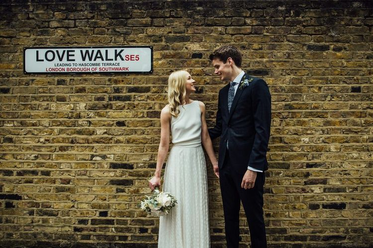 Bride and Groom London City Wedding in White Satin Dress with Removable Polka Dot Overskirt and Love Walk Road Sign