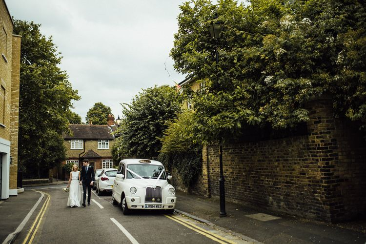 White Taxi Cab with White Ribbon Transport to Summer City London Wedding Reception Wearing Manolo Blahnik Wedding Shoes