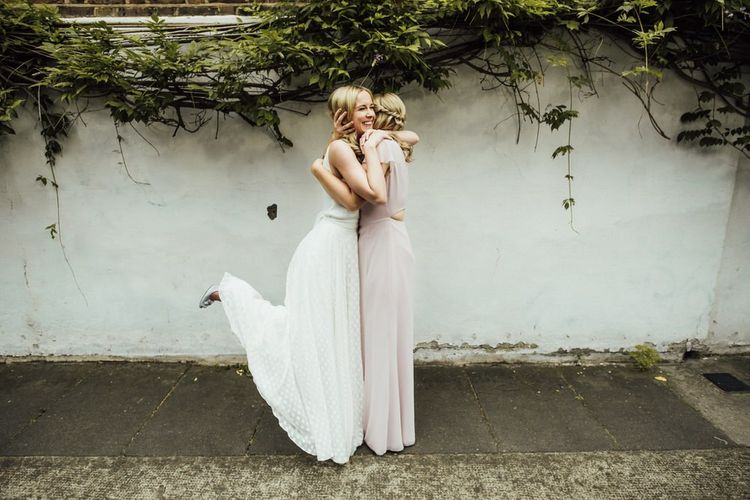 Bride in Manolo Blahnik Wedding Shoes and Satin Wedding Dress with Bridesmaid in Nude Dress at Summer City Wedding