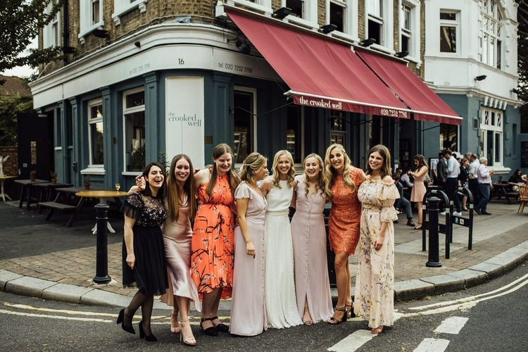 Bridal Party at Pub Reception in London with White Satin Wedding Dress and Manolo Blahnik Wedding Shoes