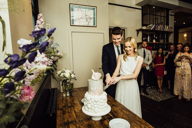 Bride and Groom Cutting the Cake with Pink and Purple Wedding Flower Decorations