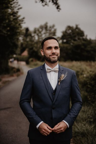 Grooms bow ties and blue wedding suit