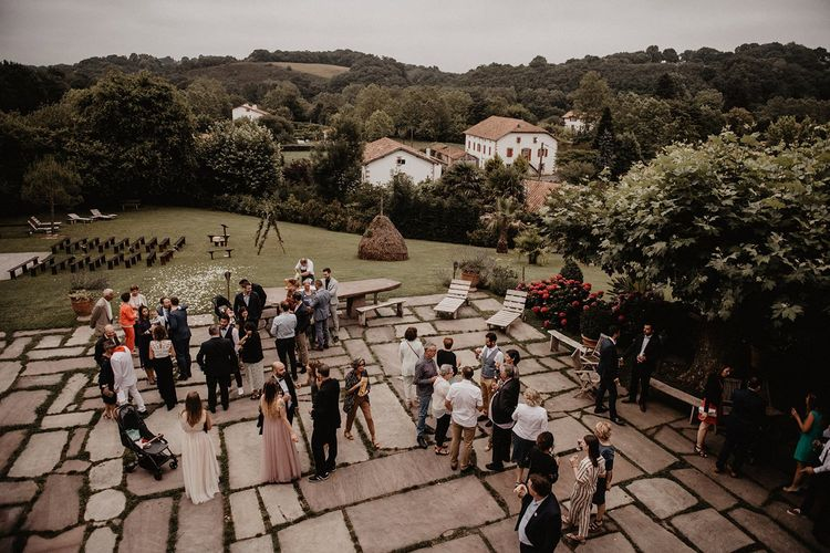 Guests enjoy drinks outdoors at French wedding venue