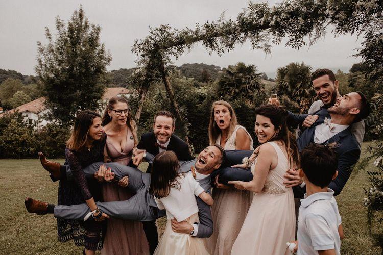 Guests pose under wedding arch