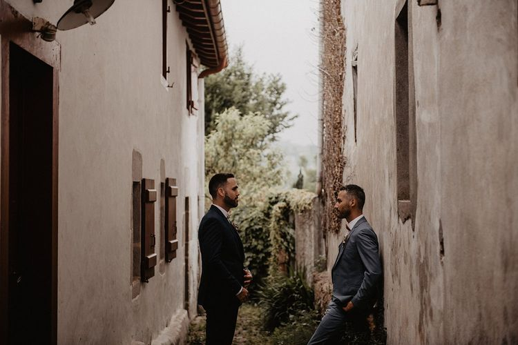 Grooms in bow ties take a moment before ceremony