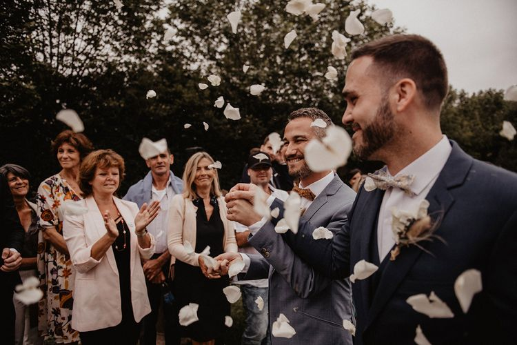 Confetti moment for grooms bow ties and wedding suits