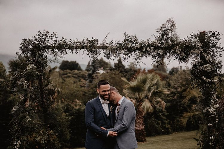 Grooms bow ties and wedding suits under wooden arch