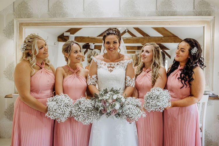 Pink halter neck bridesmaid dresses with white flower bouquet
