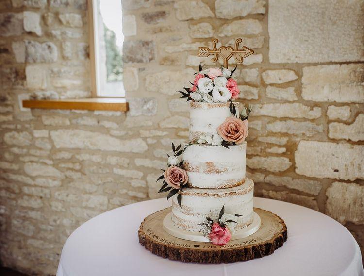 Semi-naked wedding cake on rustic wedding cake stand