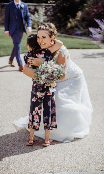 Bride hugs guests at wedding