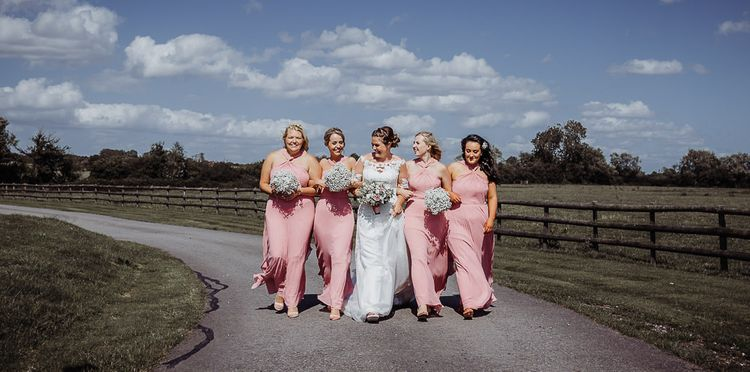 Bride in Justin Alexander wedding dress with bridesmaids in pink dresses