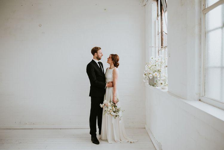 Bride in KATYA KATYA wedding dress and groom in black suit for minimalist wedding