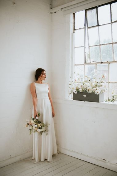 Bride standing next to a flower box filled with delicate white flowers