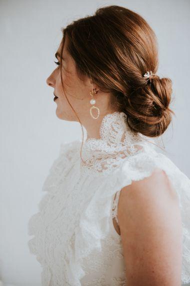 Stylish bride in sleeveless wedding dress with pinned up do