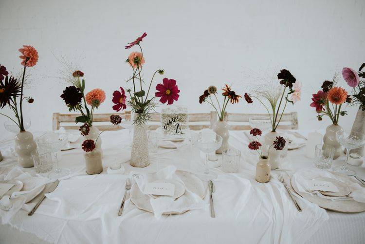 Deep red wedding flower stems in vessels as table centrepieces