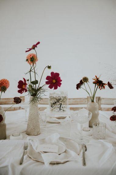 Vases and ink well centrepieces filled with flower stems for minimalist wedding