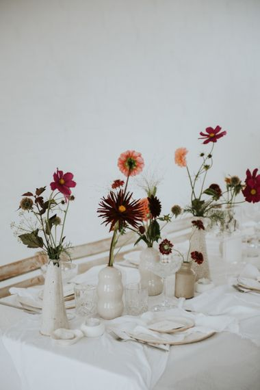 Deep pink and red flower stems in ceramic pots as table centrepieces