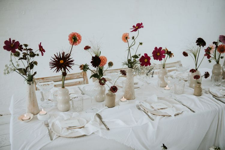 all white wedding table decor with colourful wedding flowers