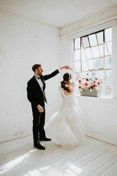Groom in tuxedo twirling his bride in a KATYA KATYA dress
