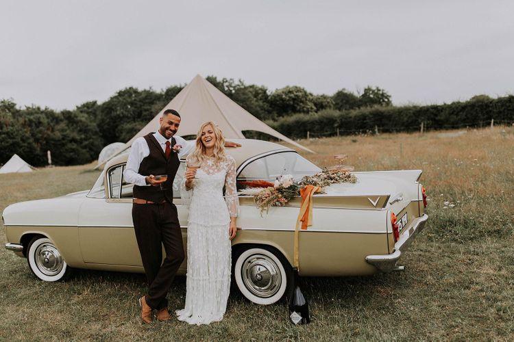Boho Bride and Groom Standing Next to a Vintage Wedding Car