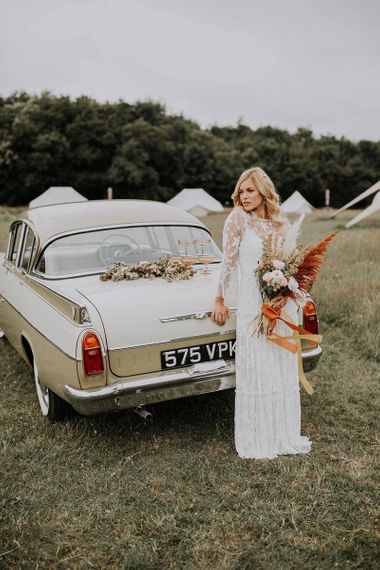 Boho Bride in Lace Wedding Dress Standing Next to a Vintage Wedding Car