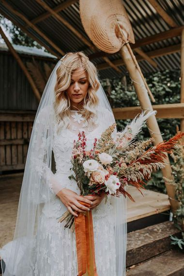 Boho Bride in Lace Wedding Dress Holding a Natural Wedding Bouquet with Roses and Pampas Grass
