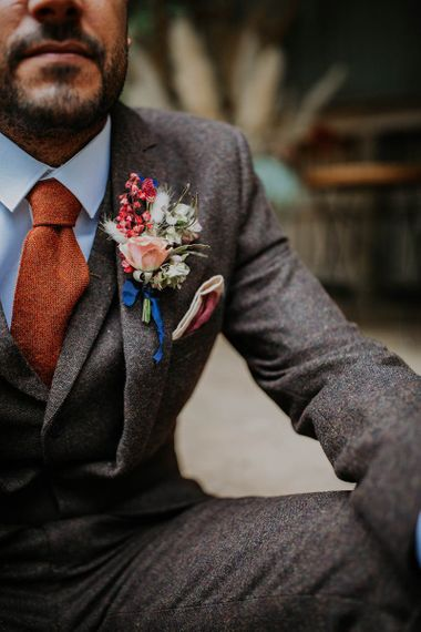 Groom in Brown Wool Suit with Orange Tie and Buttonhole