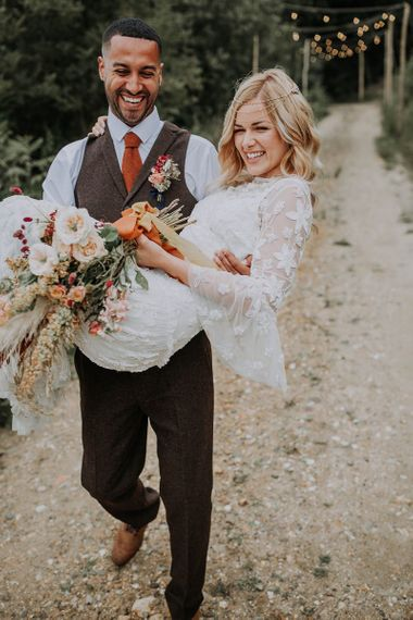 Groom in Wool Waistcoat Holding His Bride in an Applique Wedding Dress