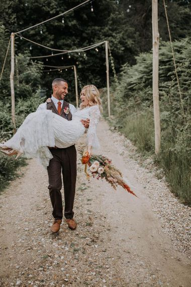 Groom in Wool Suit Picking Up His Bride in a Lace Wedding Dress