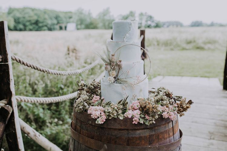 White Wedding Cake with Flower Skirt on a Wooden Barrel