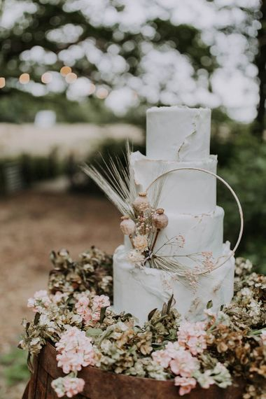White Wedding Cake with Dried Flower and Hoop Decor on a Wooden Barrel
